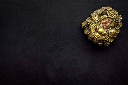 Buddhist symbol. Oriental three legged toad with gold coins on black background top view space for text Stock Photo