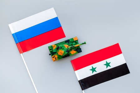 War, confrontation concept. Russia, Syria. Tanks toy near russian and Syrian flag on grey background top view.