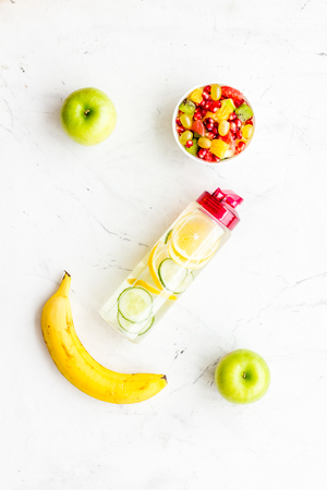 Diet rich in fruits. Slimming diet. Fruit salad near fruit lemon and cucumber water on white background top view. Stock Photo