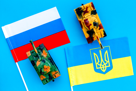 War, confrontation concept. Russia, Ukraine. Tanks toy near russian and Ukrainianflag on blue background top view.