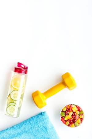 Healthy lifestyle, healthy habits. Detox water, fruit salad, sport equipment dumbbells on white background top view.