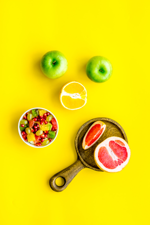 Healthy diet concept. Fruit salad near fresh fruits on yellow background top view. Stock Photo