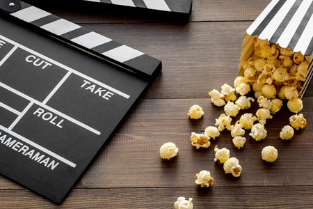 Movie premiere concept. Clapperboard and popcorn on dark wooden background. Banque d'images - 116741275