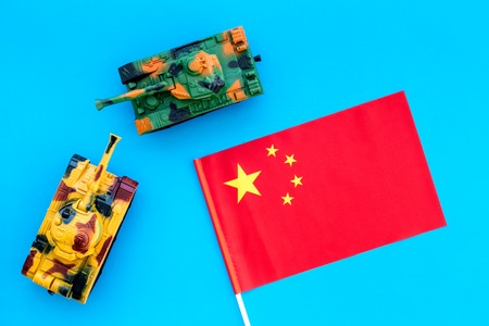 War, military threat, military power concept. China. Tanks toy near chinese flag on blue background top view. Stock Photo