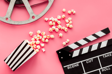 Movie premiere concept. Clapperboard, film stock, popcorn on pink background top view. Banque d'images - 116741283