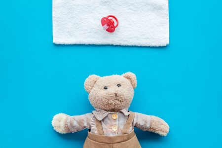 Baby care. Newborn baby concept. Teddy bear toy near pacifier on blue background top view.