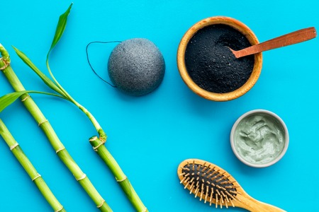 Hair care, hair spa. Cosmetics based on bamboo charcoal powder near comb on blue background top view.