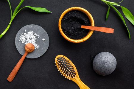 Hair care, hair spa. Cosmetics based on bamboo charcoal powder near comb on black background top view. Stock Photo - 116816516