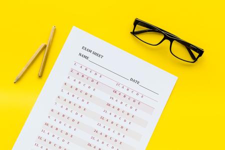 Auf der Prüfung. Prüfungsblatt, Antwort in der Nähe von Brille und Bleistift auf gelbem Hintergrund Draufsicht
