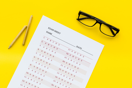 On the exam. Exam sheet, answer near glasses and pencil on yellow background top view
