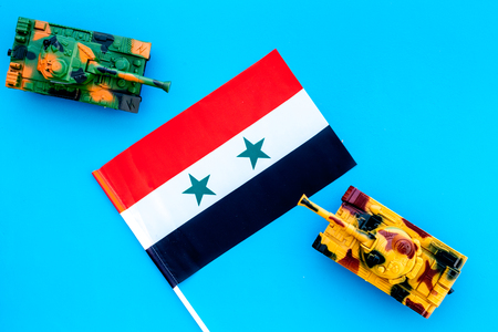 War, military threat, military power concept. Syria. Tanks toy near Syrian flag on blue background top view