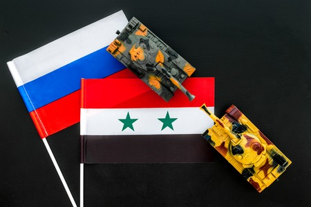 War, confrontation concept. Russia, Syria. Tanks toy near Russian and Syrian flag on black background top view