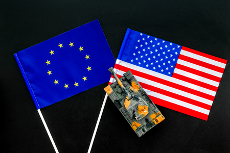War, confrontation concept. European Union, USA. Tanks toy near European and American flag on black background top view