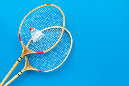 Badminton concept. Badminton rackets and shuttlecock on blue background top view copy space