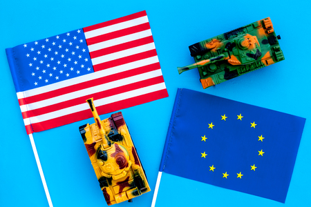 War, confrontation concept. European Union, USA. Tanks toy near European and American flag on blue background top view