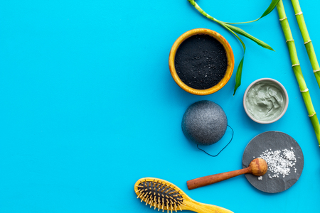 Hair care, hair spa. Cosmetics based on bamboo charcoal powder near comb on blue background top view copy space