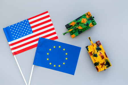 War, confrontation concept. European Union, USA. Tanks toy near European and American flag on grey background top view Фото со стока