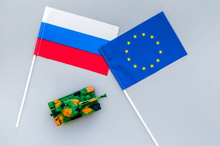 War, confrontation concept. European Union, Russia. Tanks toy near European and Russian flag on grey background top view