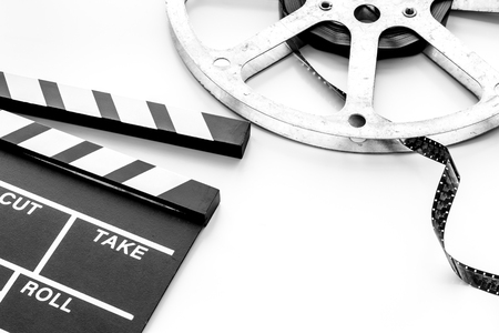 Cinema concept. Clapperboard and film stock on white background copy space
