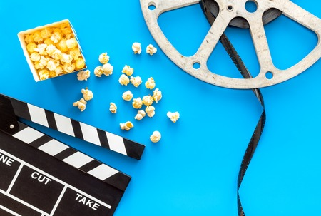 Cinema concept. Clapperboard, film stock, popcorn on blue background top view Banque d'images - 116816589