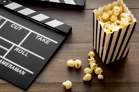 Movie premiere concept. Clapperboard and popcorn on dark wooden background