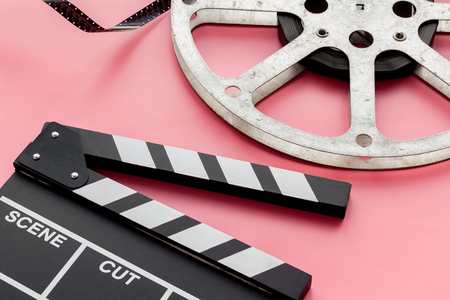 Cinema concept. Clapperboard, film stock on pink background