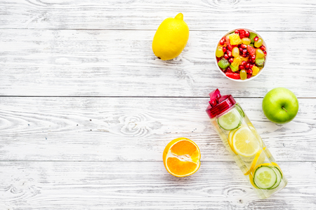 Diet rich in fruits. Slimming diet. Fruit salad near fruit lemon and cucumber water on white wooden background top view copy space