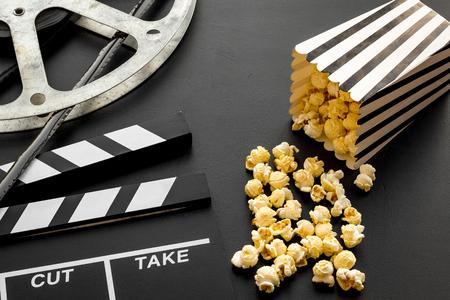Cinema concept. Clapperboard, film stock and popcorn on black background