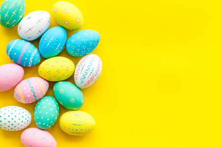 Easter composition. Decorated pastel Easter eggs on yellow background copy space border Standard-Bild