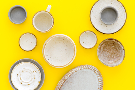 Kitchen concept. Crockery kit. Empty ceramic plates and mugs on yellow background top view
