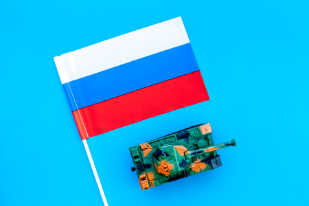 War, military threat, military power concept. Russia. Tanks toy near russian flag on blue background top view 版權商用圖片