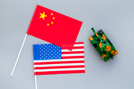 War, confrontation concept. China, USA. Tanks toy near chinese and american flag on grey background top view Stock Photo