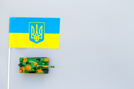 War, military threat, military power concept. Ukraine. Tanks toy near Ukrainian flag on grey background top view copy space