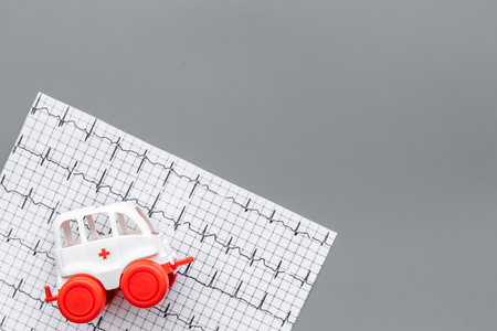 Emergency care concept. Ambulance vehicle toy near cardiogram on grey background top view space for text