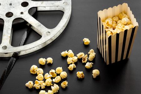 Concetto di cinema. pellicola e popcorn su sfondo nero.