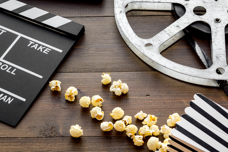 Cinema concept. Clapperboard, film stock and popcorn on dark wooden background.