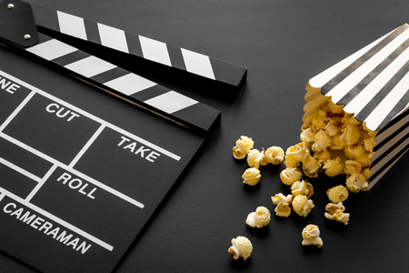 Movie premiere concept. Clapperboard and popcorn on black background. Stock fotó