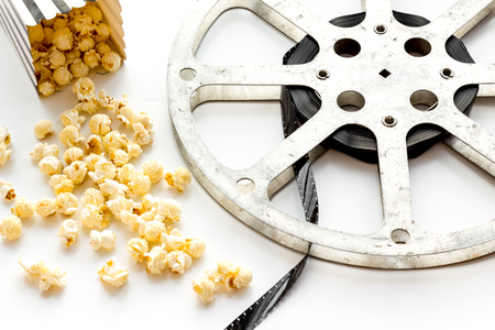 Cinema concept. film stock and popcorn on white background. Banque d'images - 116880260