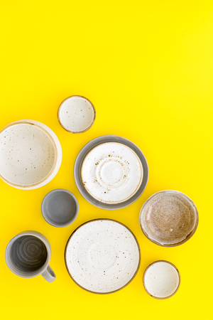 Ceramic tableware pattern. Empty plates and mugs on yellow background top view copy space