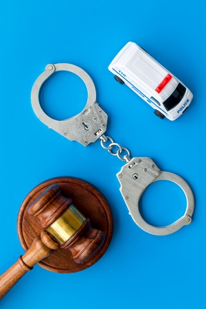 Crime concept. Police car toy, handcuff, judge hammer on blue background top view Stock Photo