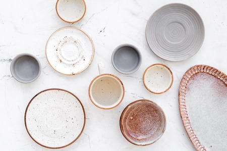 Kitchen concept. Crockery kit. Empty ceramic plates and mugs on white background top view Stock Photo