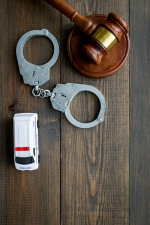 Crime concept. Police car toy, handcuff, judge hammer on dark wooden background top view space for text 스톡 콘텐츠