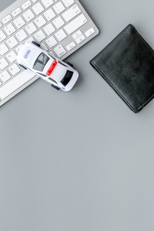 Call police online concept. Police car toy and computer keyboard on grey background top view space for text
