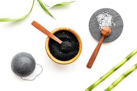 Skin cleansing and detox. Bamboo charcoal powder cosmetics on white background top view