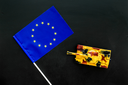 War, military threat, military power concept. European Union. Tanks toy near european flag on black background top view copy space Stock Photo - 117040582