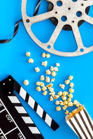 Cinema concept. Clapperboard, film stock, popcorn on blue background top view Banque d'images - 117040651