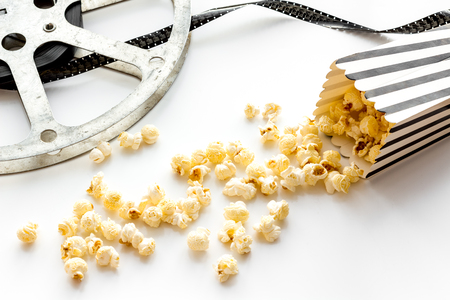 Cinema concept. film stock and popcorn on white background. Banque d'images - 117040629