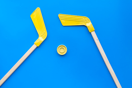 Ice hockey stick and puck on blue background top view. Stock fotó