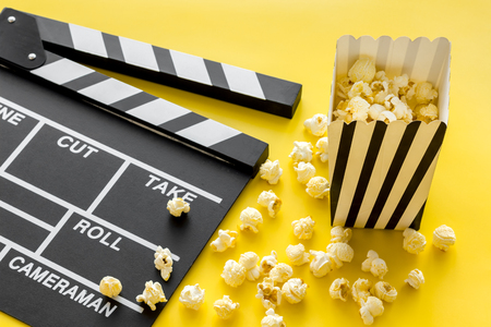 Movie premiere concept. Clapperboard and popcorn on yellow background.
