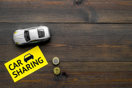 Car sharing concept, car sharing sign. Economical, chip trip. Toy car near coins on dark wooden background top view copy space